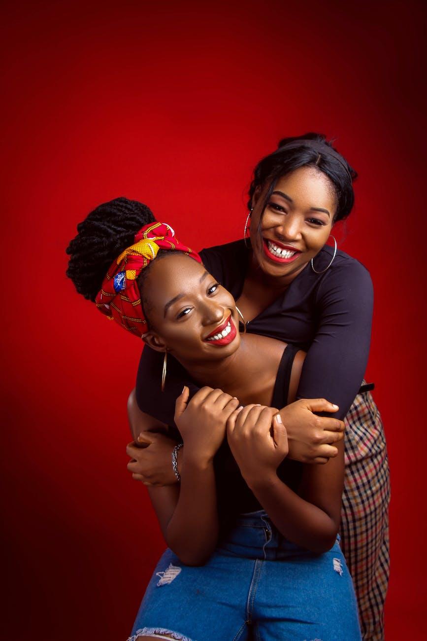 smiling black women embracing in studio